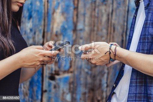 Couple`s hands using smartphone