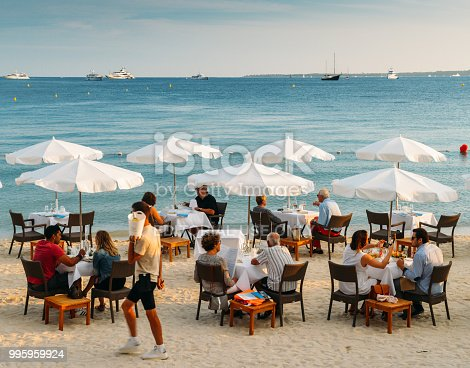 Juan les Pins, France - July 7th, 2018: Couples have drinks and appetizers at a luxurious restaurant on the beach in the French Riviera resort town of Juan les Pins, Cote d'Azur, France