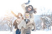Young people having fun in piggyback ride in snow forest. Wear warm clothes, sunglasses and gloves. Looking at camera.