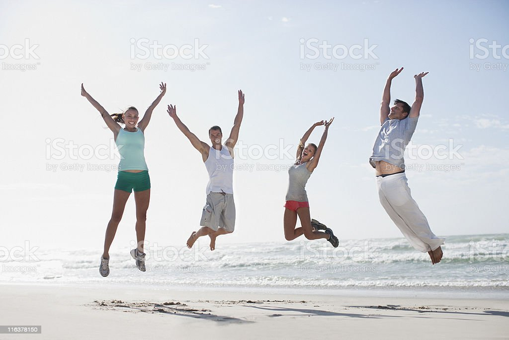 Couples jumping on beach royalty-free stock photo