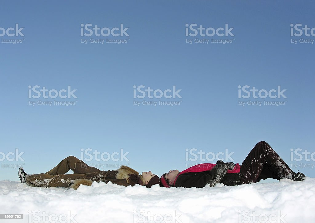 couples lies on snow and watch up stock photo