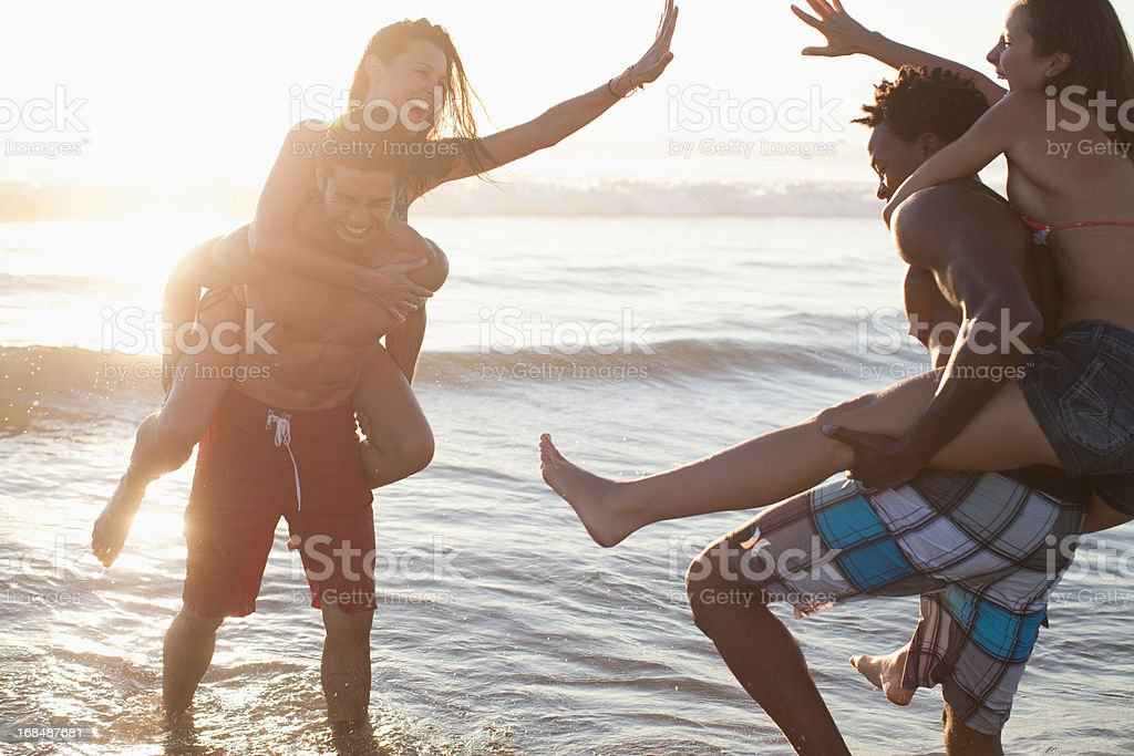Couples playing in waves on beach royalty-free stock photo