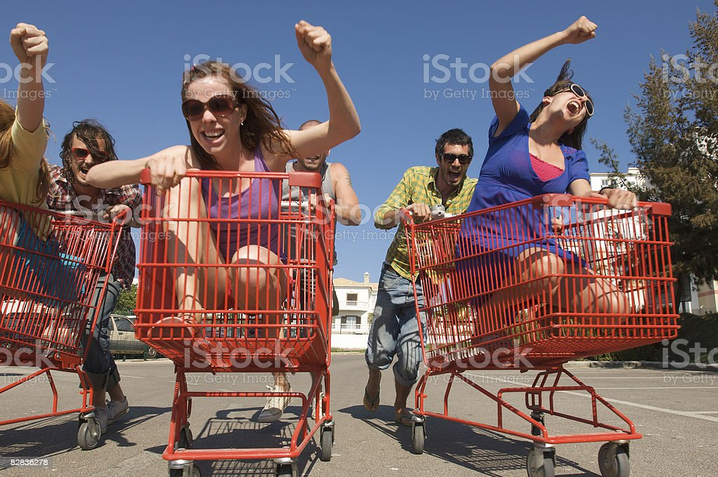 couples racing supermarket trolleys royalty free stockfoto