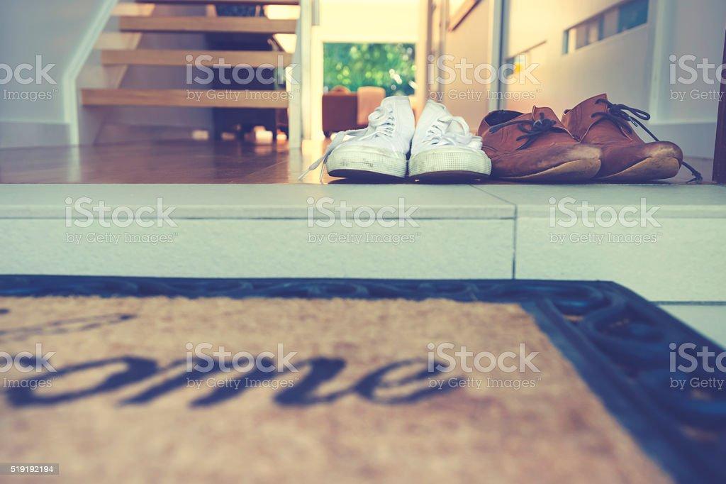 Parejas Zapatos en la puerta principal de una casa. - foto de stock