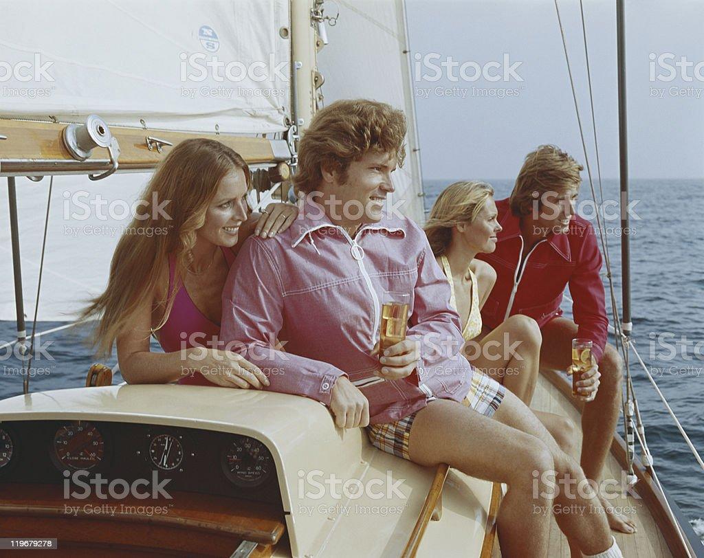 Couples sitting on sailing boat, smiling stock photo