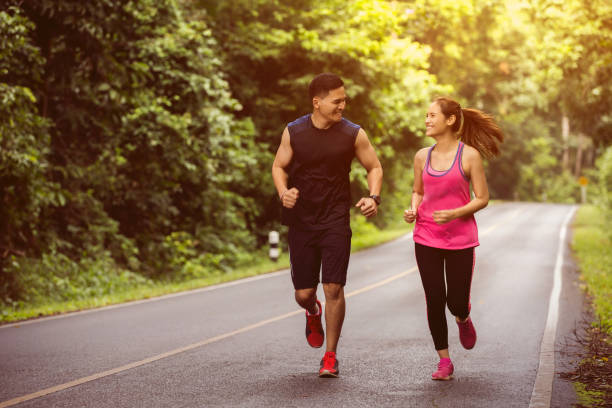 Couples take vacations jogging in the forest. The integrity and refreshing stock photo