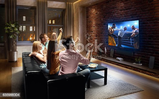 :biggrin:Two couples are cheering while watching Boxing at home. They are sitting on a sofa in the modern living room faced to a big TV set on the front wall.