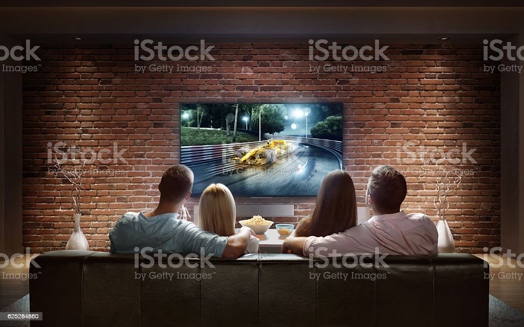 Couples watching car race game at home stock photo