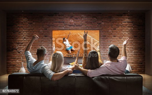istock Couples watching Tennis game at home 627645572