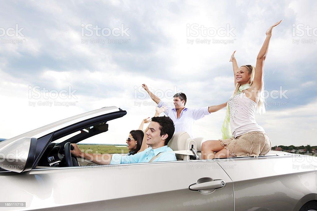 Paare mit erhöhter Hände in ein cabriolet fahren. – Foto