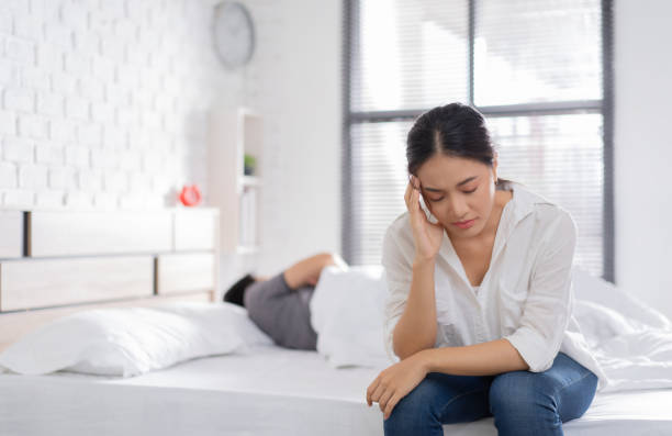 couple,they have problems with quarrel. woman sitting in bed She is having a headache stock photo