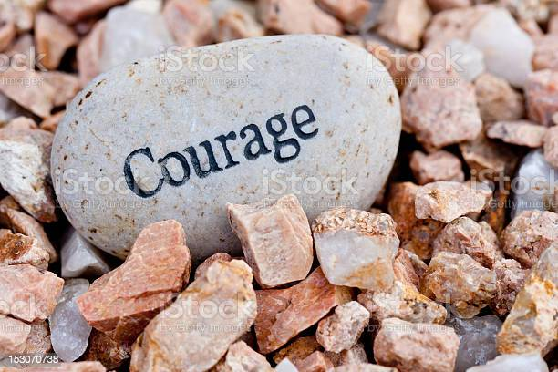 Photo of Courage written on a big smooth rock with jagged rocks