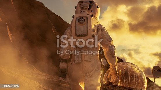 istock Courageous Astronaut in the Space Suit Explores Red Planet Mars Covered in Mist. Shelter in background. Space Travel, Colonization Concept. 930523124