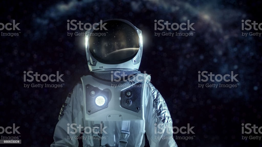 Courageous Astronaut in the Space Suit Stands on the Alien Planet. Milky Way Galaxy Behind Him. Exploring Newly Discovered Planet. Space Travel and Extraterrestrial Colonization Concept. stock photo