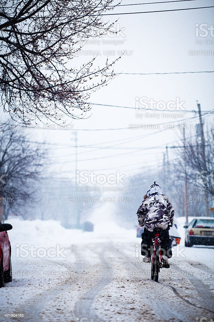 Courageous biker during a winter storm - editorial royalty-free stock photo