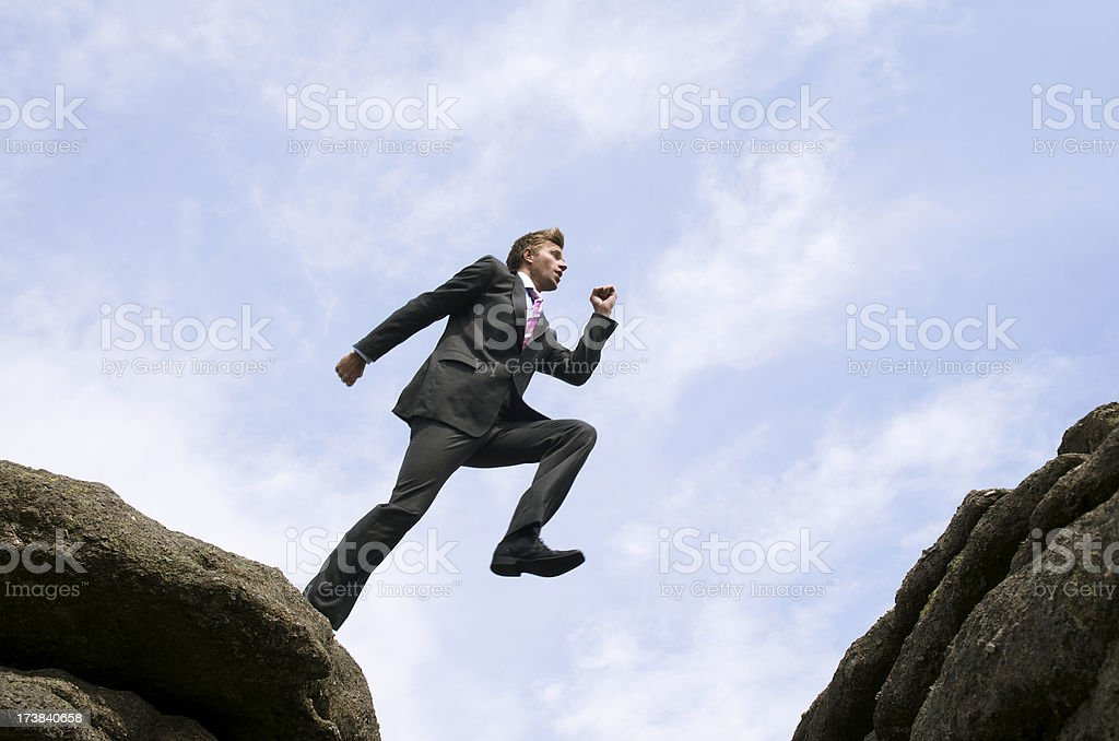 Courageous Businessman Jumping Over Rock Chasm royalty-free stock photo