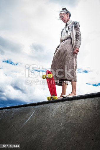 A senior elderly woman attempting skateboarding stands at the edge of a halfpipe debating whether to drop in.   A great additional exercise and balance for her healthy lifestyle.