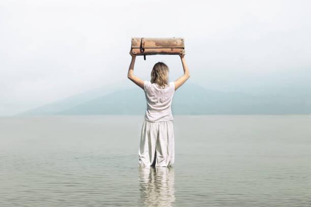 courageous woman walks towards the infinite in the sea - donna valigia solitudine foto e immagini stock