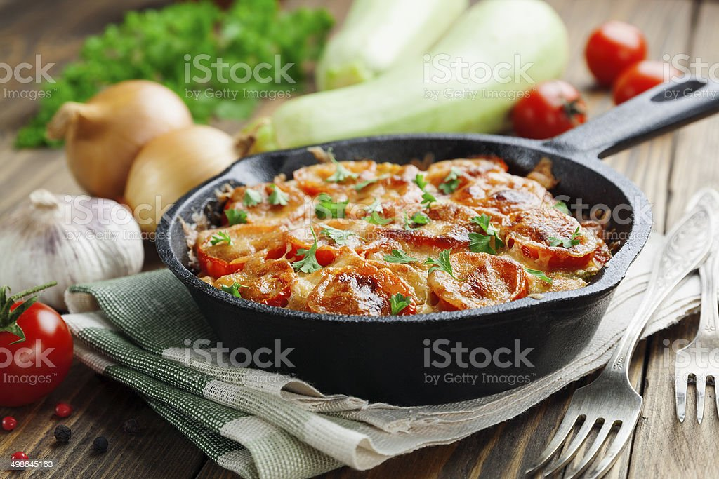 Courgettes baked with tomato and cheese royalty-free stock photo