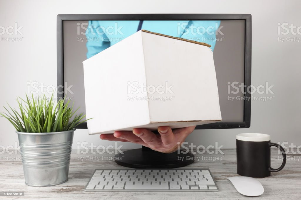 Courier arm coming out of computer screen with white package - foto stock