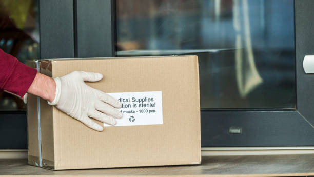 courier brings a box with protective medical masks to the doorstep - essential workers stock pictures, royalty-free photos & images