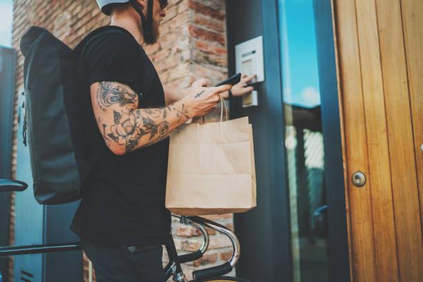 Kurier Stadt liefert Lebensmittelservice zu Hause. Tätowierte Man Kurier lieferte die Bestellung keine Namensbeutel mit Lebensmitteln – Foto