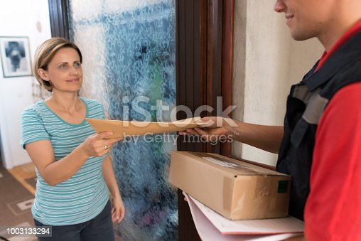istock Courier Delivering a Package 1003133294