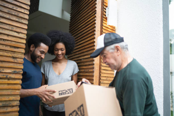 courier delivering boxes to a young couple - being in a relationship with someone is going to require stock photos and pictures