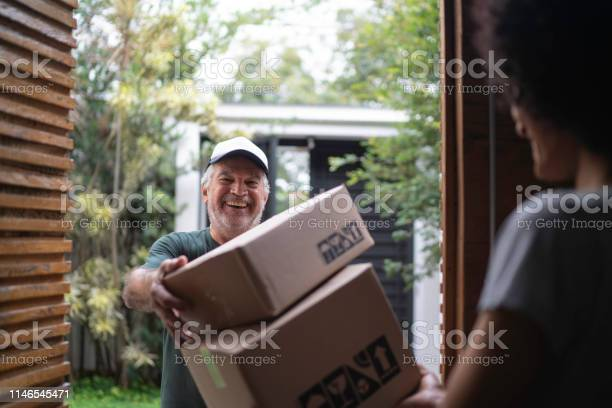 Courier delivering boxes to a young woman picture id1146545471?b=1&k=6&m=1146545471&s=612x612&h=htwn7fb53m7yva5nl9  nac54kj87fed7mgvxm t h0=