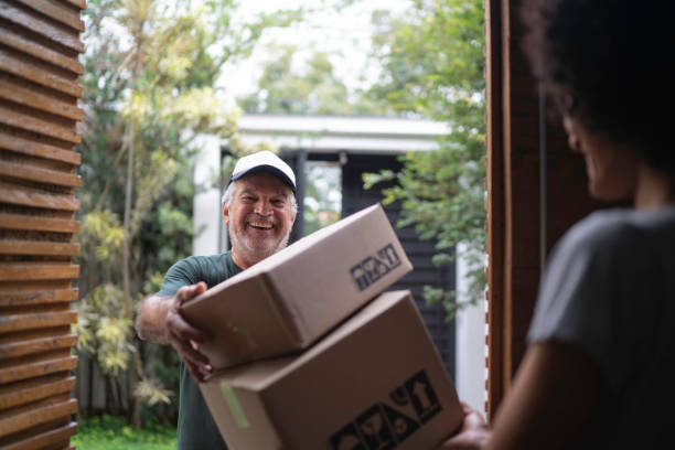 Courier delivering boxes to a young woman Courier delivering boxes to a young woman delivery man stock pictures, royalty-free photos & images