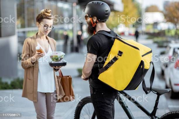 Courier delivering food to a business woman outdoors picture id1177038171?b=1&k=6&m=1177038171&s=612x612&h=eqphjd35vw9gikodkwe i9gnnf3ckxels2a8gqge2yq=