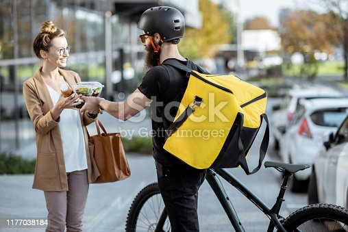 istock Courier delivering food to a business woman outdoors 1177038184