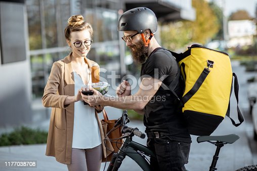 istock Courier delivering food to a business woman outdoors 1177038708