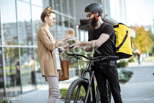 istock Courier delivering food to a business woman outdoors 1177038725