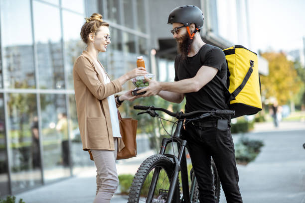 courier delivering food to a business woman outdoors - food delivery imagens e fotografias de stock