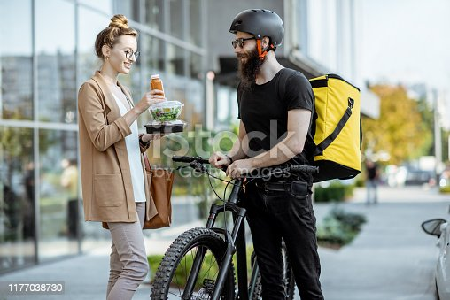 istock Courier delivering food to a business woman outdoors 1177038730