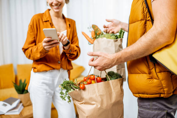 Courier delivering groceries home stock photo
