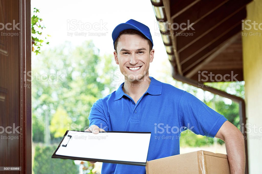Courier delivering package Delivery man standing at the door of the house and carrying parcel, holding clipboard in hand, smiling at camera. Adult Stock Photo