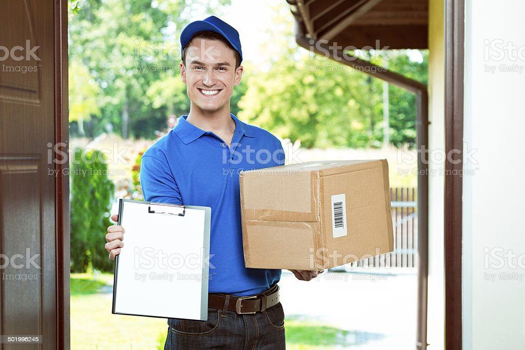 Courier delivering package Delivery man standing at the door of the house and carrying parcel, holding clipboard in hand, smiling at camera. Fabricated bar code. Adult Stock Photo