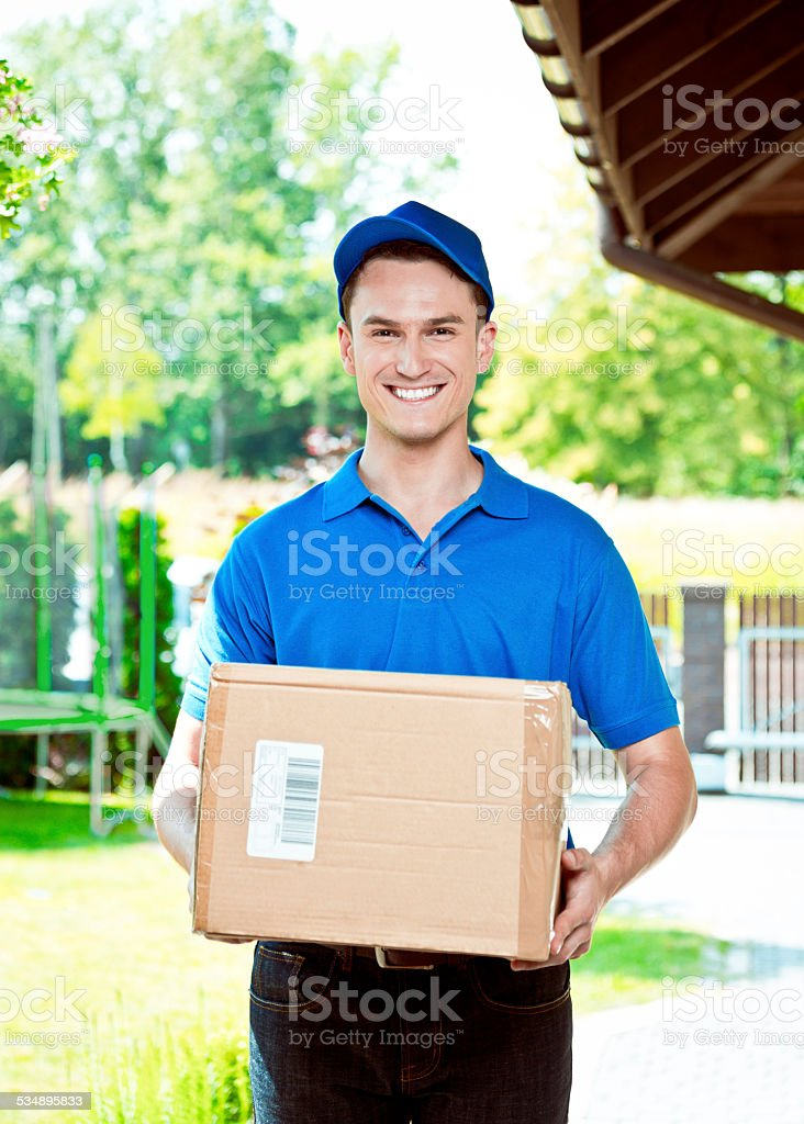 Courier delivering package Delivery man standing outdoor and carrying parcel, smiling at camera. 2015 Stock Photo