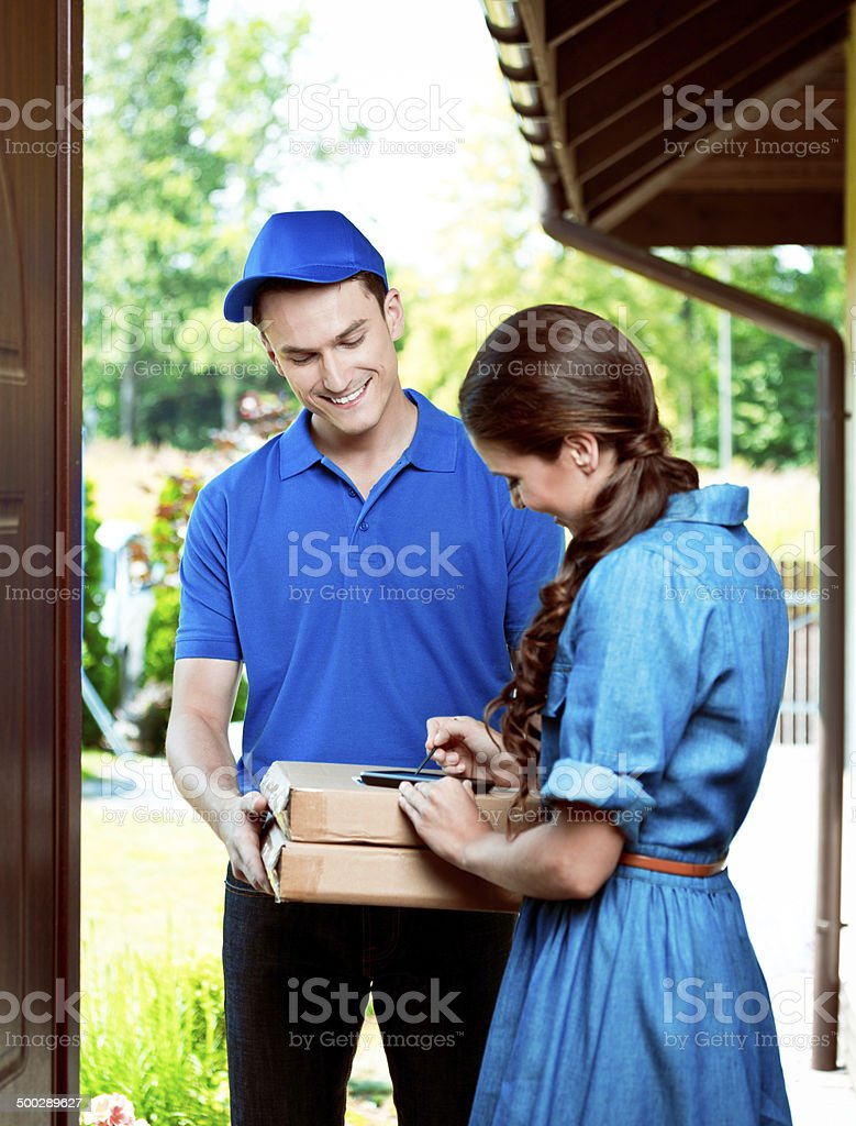 Courier delivering packages Delivery man standing at the door of the house and carrying parcels for young woman. Adult Stock Photo