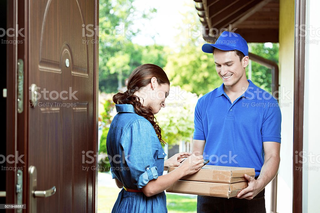 Courier delivering packages Delivery man standing at the door of the house and carrying parcels for young woman. Woman signing. Adult Stock Photo