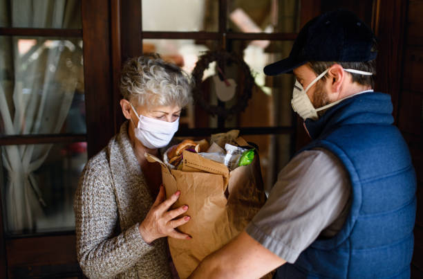 Courier delivering shopping to senior woman with face mask, corona virus and quarantine concept. stock photo