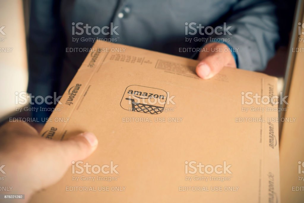 courier delivers an Amazon package to a costumer stock photo