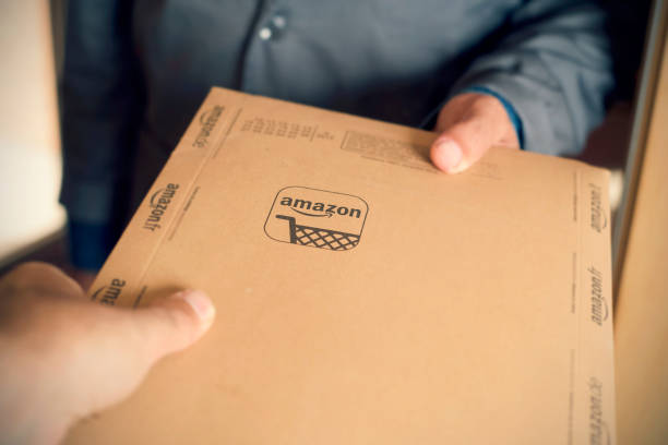 courier delivers an Amazon package to a costumer Barcelona, Spain - November 2, 2017: A courier delivers an Amazon package to a costumer. Amazon is an important worldwide online shopping company based in the United States amazon stock pictures, royalty-free photos & images
