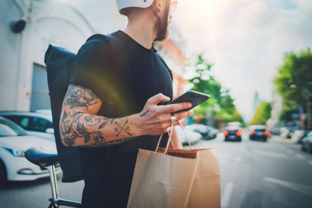 Kurier-Lieferung Lebensmittelservice zu Hause. Mann Kurier mit einer Karte-App auf Handy, um die Lieferadresse in der Stadt zu finden – Foto