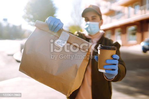 istock Courier in protective mask and medical gloves holds out paper packet with food and cofee. 1223012863