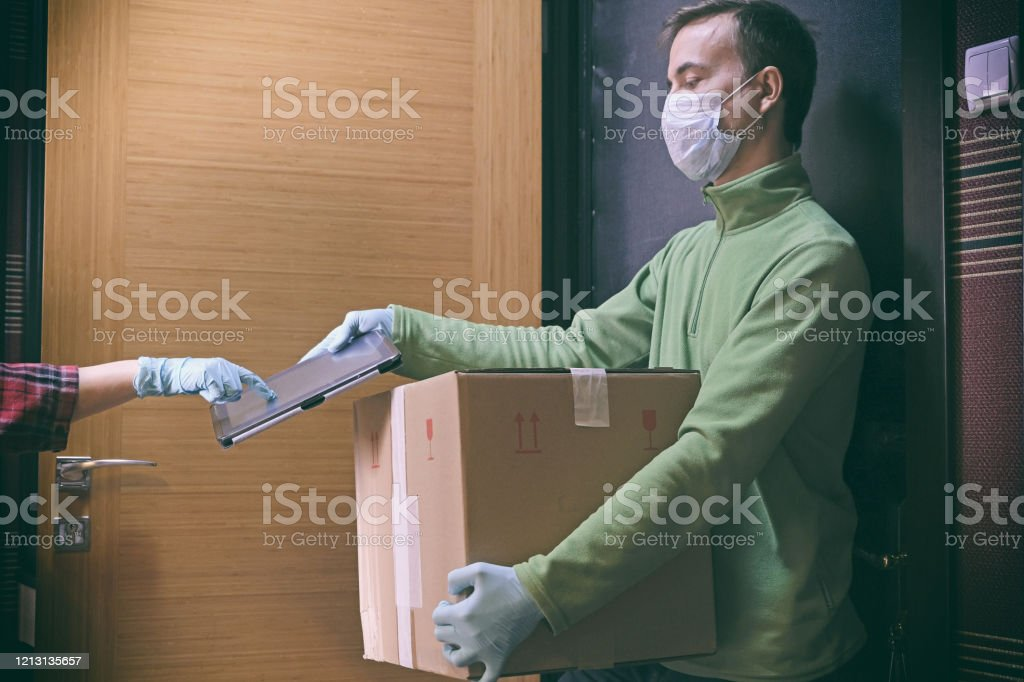 Courier in protective mask delivers parcel to client, client in medical gloves signs on tablet. Delivery service under quarantine, disease outbreak, coronavirus covid-19 pandemic conditions. - Foto stock royalty-free di Abbigliamento