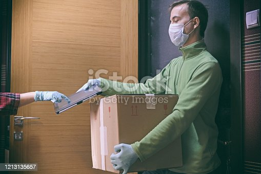 Courier in protective mask delivers parcel to client, client in medical gloves signs on tablet. Delivery service under quarantine, disease outbreak, coronavirus covid-19 pandemic conditions.