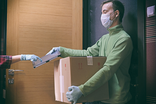 Courier In Protective Mask Delivers Parcel To Client Client In Medical Gloves Signs On Tablet Delivery Service Under Quarantine Disease Outbreak Coronavirus Covid19 Pandemic Conditions - Fotografie stock e altre immagini di Abbigliamento